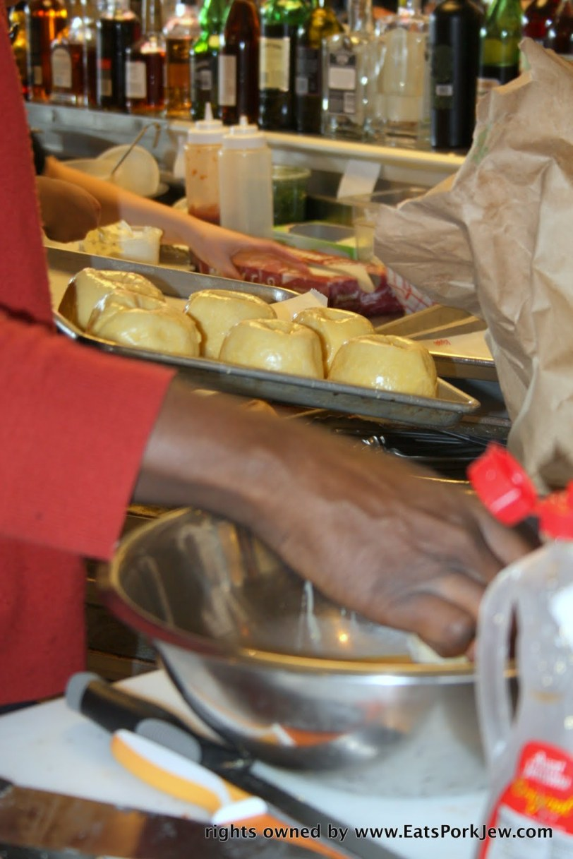 Buffalo Bergen staff member dipping knishes into an egg wash before backing at DC's Union Market