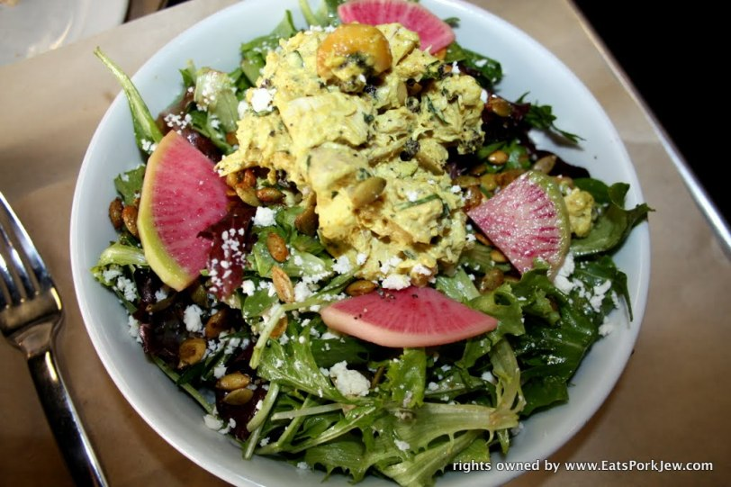 Curry chicken salad with mixed greens, chicken salad, spiced pepitas, & cotija with watermelon radishes from big bottom market in Guerneville, CA